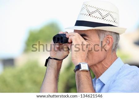 Old man looking through binoculars - stock photo