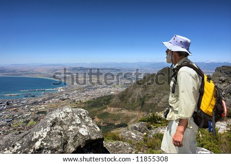 Old man looks at port city from mountain. Shot in Table Mountain (cable car area), Cape Town, South Africa. - stock photo