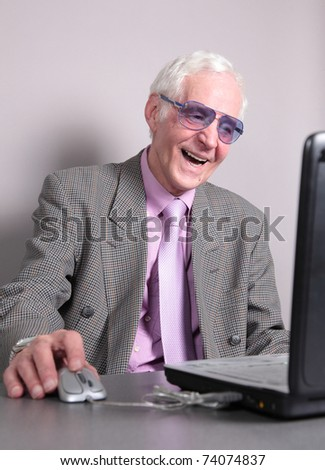 Old man looks in the screen of notebook laughs. isolated against grey background