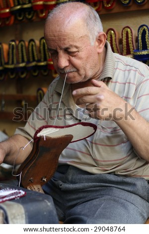 old man making handmade slippers for ladies - stock photo