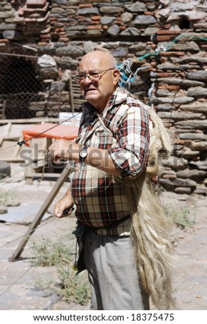old man making handmade traditional rope from felt