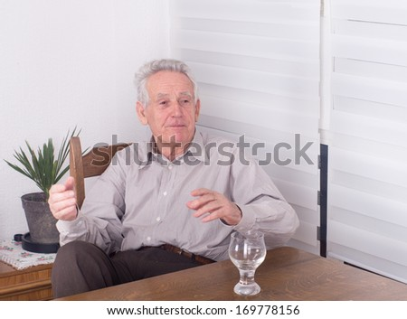 Old man moving hands while talking at dining table - stock photo