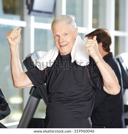 Old man on treadmill in fitness center holding his thumbs up - stock photo