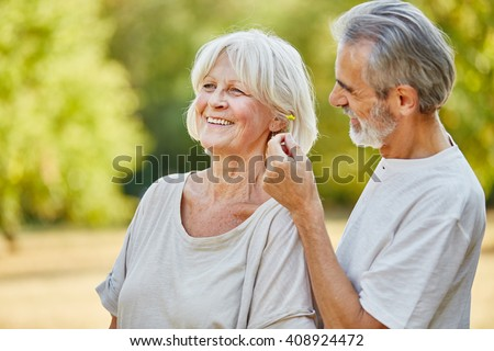 Old man picking up a flower for a woman in summer in the nature - stock photo