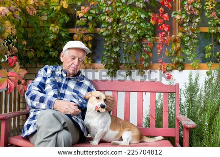 Old man playing with dog on bench in courtyard - stock photo