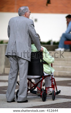 Old man pushes his wife in a wheel chair - stock photo
