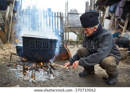 Old man putting wood on fire below large boiling cast iron pots - stock photo