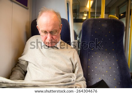 old man reading the newspaper on the train - stock photo