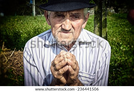 Old man's hands, praying in the yard. - stock photo