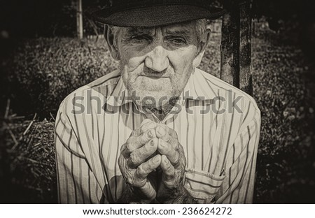 Old man's hands, praying in the yard. Sepia picture. - stock photo