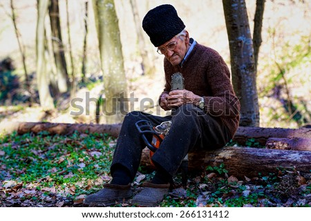 old man sharpening a chainsaw - stock photo