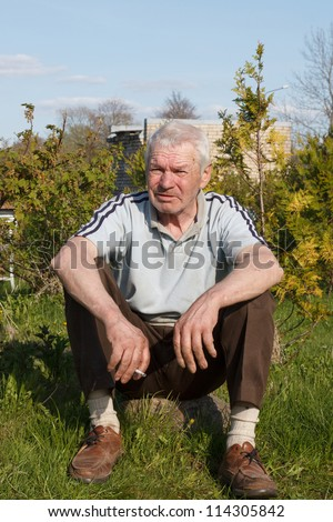 old man sitting and relax with cigarette - stock photo