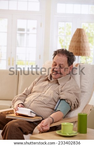 Old man sitting in armchair at home, measuring his blood pressure, smiling.  - stock photo