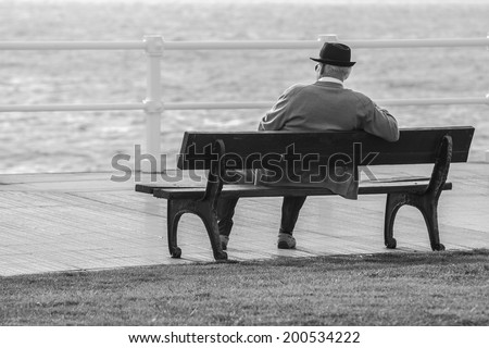 Old man sitting on a bench facing the sea - stock photo