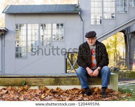 Old man sitting on bench, thinking, abandoned railroad station on background - stock photo