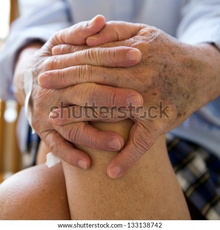 Old man sitting with his hands on knee. - stock photo