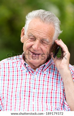 Old man smiling and talking on cell phone - stock photo
