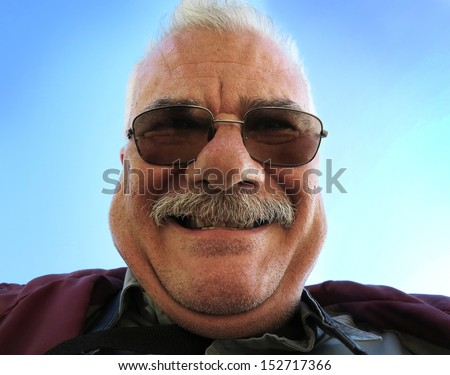 Old man smiling with sunglasses in funny pose                               - stock photo