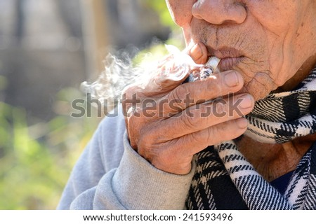 Old man smoking - stock photo