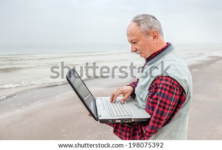 old man standing on the beach with a laptop on a foggy day