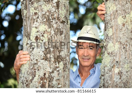 Old man  stood between two trees - stock photo