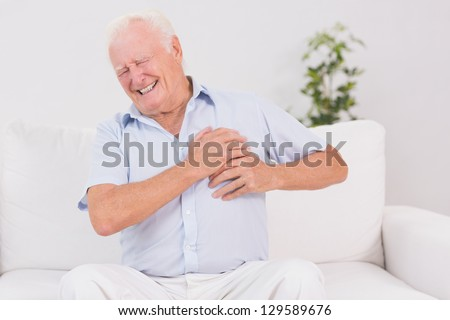 Old man suffering with heart pain on a sofa - stock photo