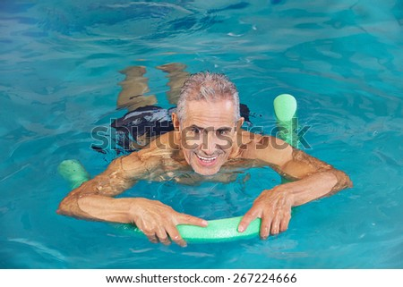 Old man swimming in water of hotel pool with swim noodle - stock photo