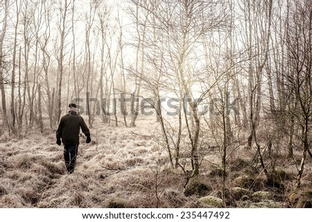 Old man taking a morning walk in misty nature - stock photo
