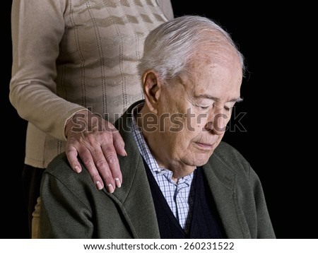 Old man, thoughtfully, with his wife's hand over his shoulder - stock photo