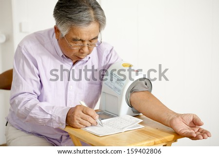 Old man to the control of blood pressure on your own - stock photo