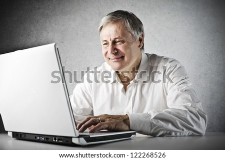 Old man using a laptop computer - stock photo