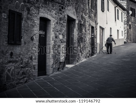 Old man walking in a medieval street in Tuscany, Italy - stock photo