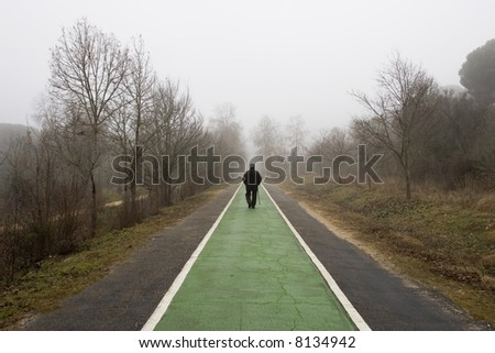 Old man walks on the cycleway to the mist - stock photo