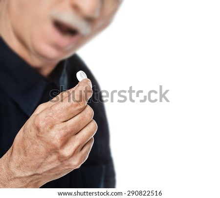 Old man wants to take a pill. Focus on hand. Isolated on white background with copy-space