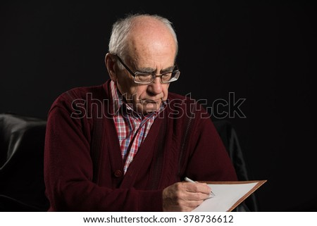 old man wearing eyeglasses writing some notices with pan and white paper - stock photo