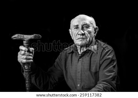 old man with a carved wooden cane - stock photo