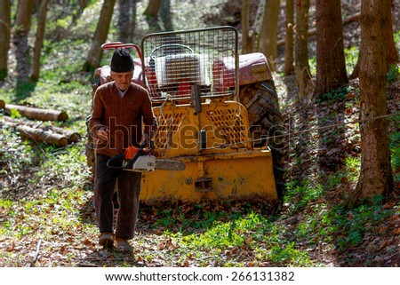 old man with a chainsaw in the forest - stock photo
