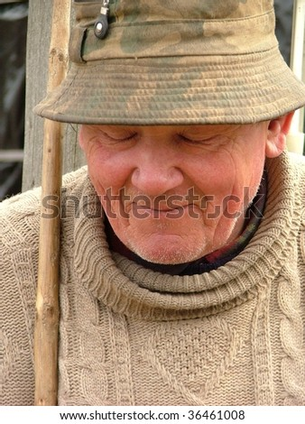 Old man with a hat and a walking stick - stock photo