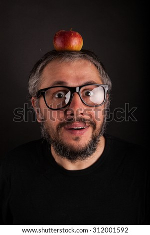 Old Man with beard and big nerd glasses with apple on head is surprised