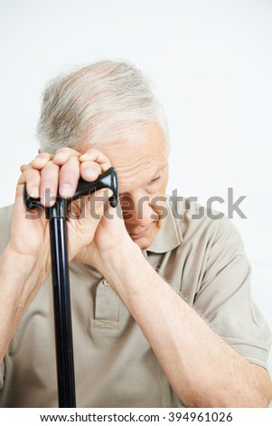 Old man with depression putting his hands on a cane - stock photo