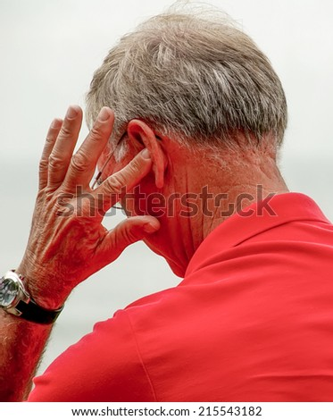 old man, with hearing problems resolved - stock photo