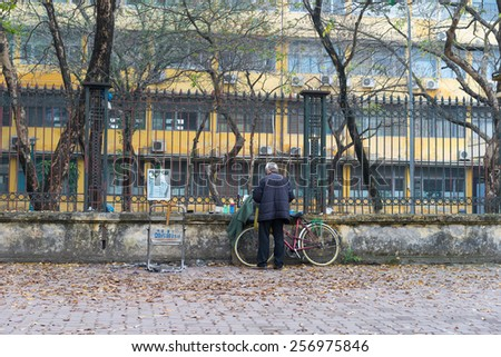 Old man with his old bike on Hanoi street in winter season - stock photo