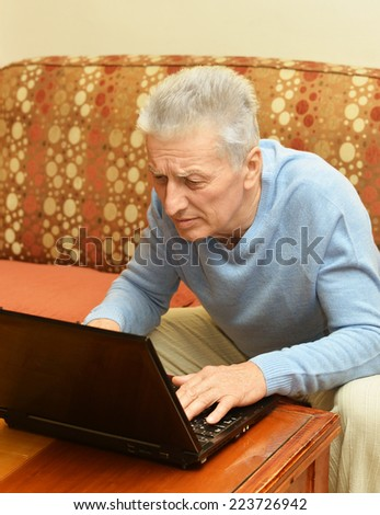 Old man with laptop at the table