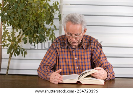 Old man with reading glasses reading book in his library