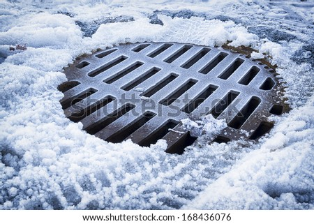 old manhole at a street in winter - stock photo