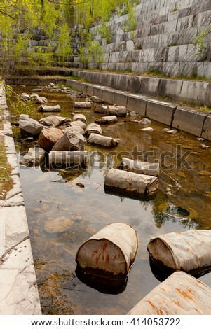 Old marble quarry, abandoned fuel barrels on bottom. Careless attitude towards nature. Industrial waste products of oil refining. Extraction of minerals by open method. - stock photo