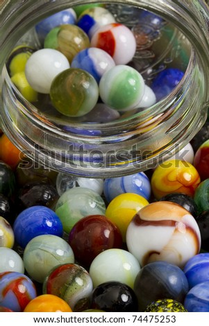 Old marbles with glass jar. - stock photo