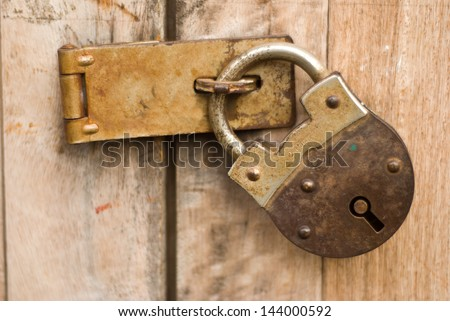 Old master key with wooden door at Chiengkarn - stock photo