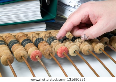 Old mathematical calculator abacus with bunch of papers - stock photo