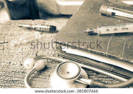 Old medical syringes , hypodermic needles and stethoscope on old black diary - stock photo